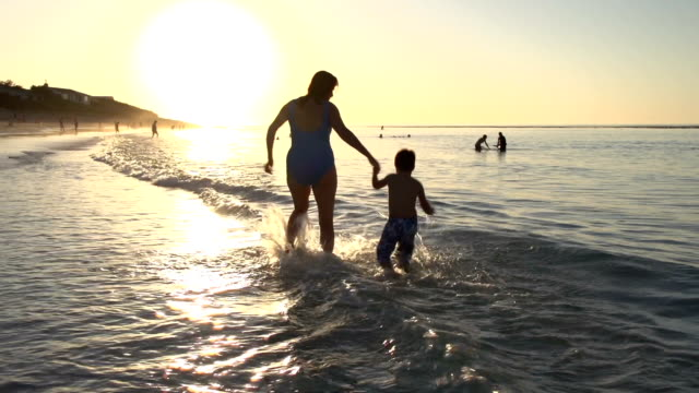 Mother and child playing on beach in silhouette at sunset,Cape Town video
