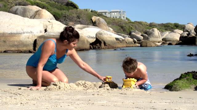 vídeos de stock, filmes e b-roll de mãe e criança brincando na praia com brinquedos, cidade do cabo - penedo