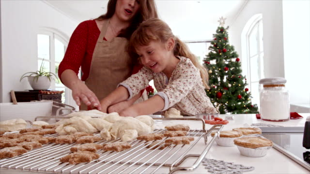 Mother and child preparing Christmas cookies Mother and child preparing Christmas cookies in kitchen. Woman and little girl kneading dough for cookies. cookie stock videos & royalty-free footage