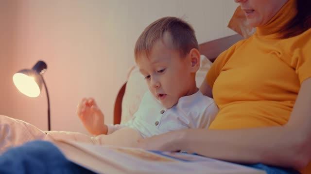 mor och barn, läsa en bok innan sängdags - cosy pillows mother child bildbanksvideor och videomaterial från bakom kulisserna