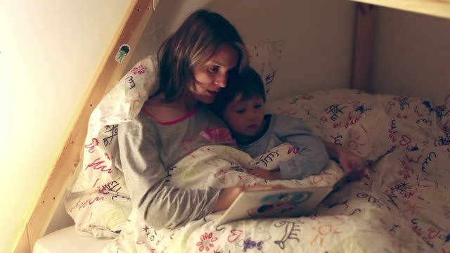 mother and child, reading a book before bed time - fiaba video stock e b–roll