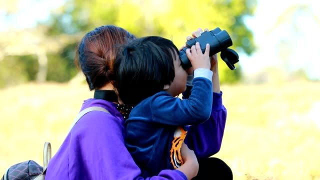 Mother and child  using binoculars in the forest, Slow motion video