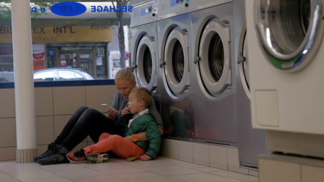 Mother and child using mobile in the laundry video