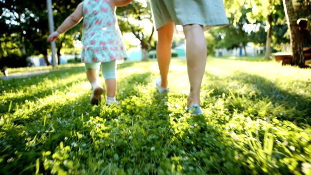 Madre y el niño caminando en la hierba - vídeo