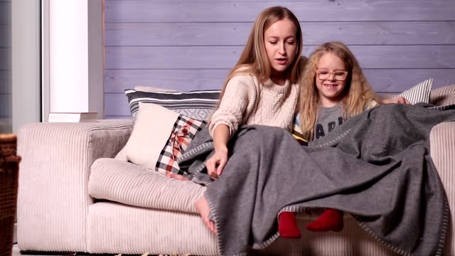 Mother and child warming up under blanket at home video