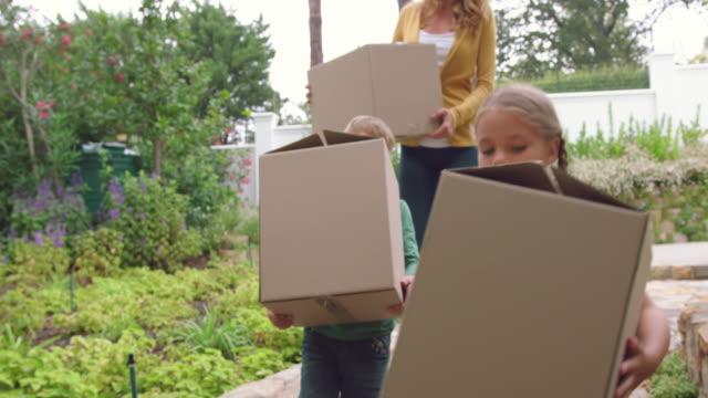Mutter und Kinder tragen Pappkartons nach Hause 4k – Video