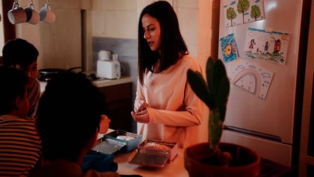 vídeos de stock, filmes e b-roll de mãe e filhos se divertindo juntos a preparar caixas de almoço - almoço