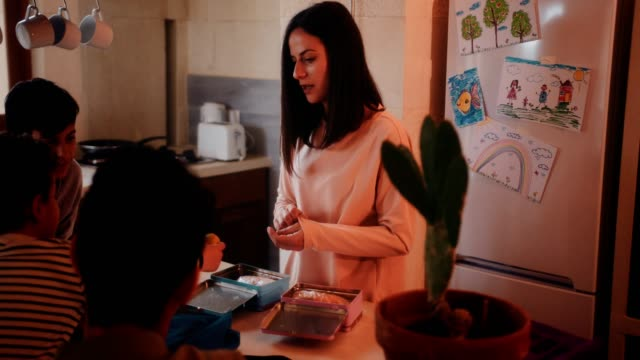 vídeos de stock e filmes b-roll de mother and children having fun preparing lunch boxes together - mochila saco