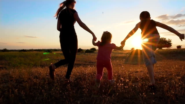 Mother and children hold hands and run at sunset in slow motion