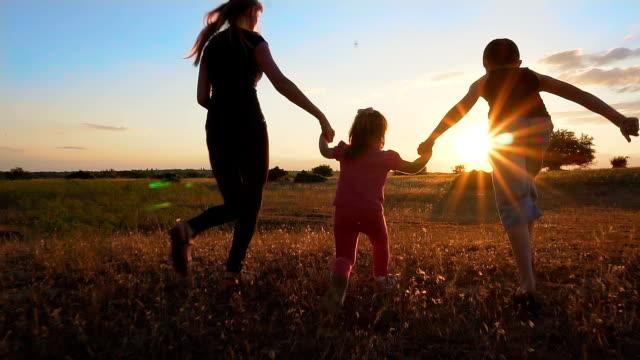 母と子の手を押しながらスローモーションで夕暮れ時を実行 - 米国旅行点の映像素材/bロール