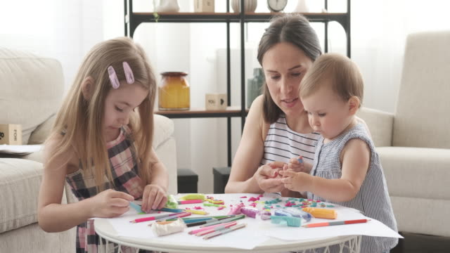 Mother and children playing with plasticine