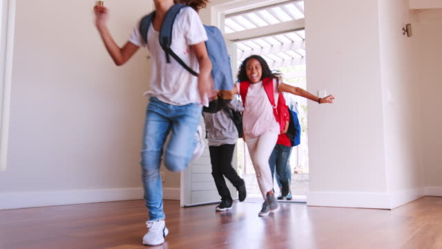 Mother And Children Returning Home After School Day Group of children running through front door of house at the end of school day followed by mother - shot in slow motion front door stock videos & royalty-free footage