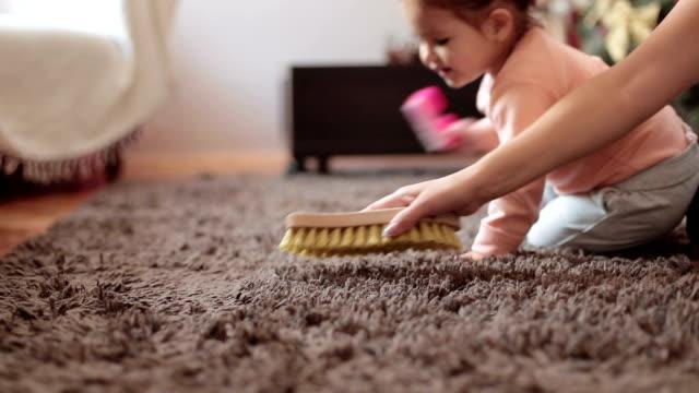 母と、敷物をブラッシングのかわいい女の子の赤ちゃんはきれいにし、彼女の母親を支援する方法を学習 - 家の雑用点の映像素材/bロール