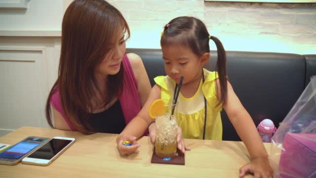 mor och dotter dricker apelsinjuice. - birthday celebration looking at phone children bildbanksvideor och videomaterial från bakom kulisserna