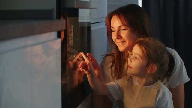 vídeos de stock e filmes b-roll de mother and daughter are looking at how to prepare homemade pizza. follow the preparation of the pie in the oven. mother and daughter together prepare a pie and bake in the oven - assado no forno