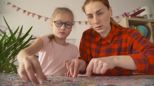 mother and daughter assembles big bright puzzle at the table - puzzle video stock e b–roll