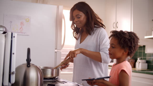 Mother And Daughter At Home Preparing Meal In Kitchen video