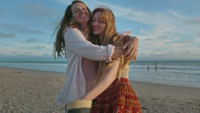 Mother and daughter at the beach hugging and smiling at camera video