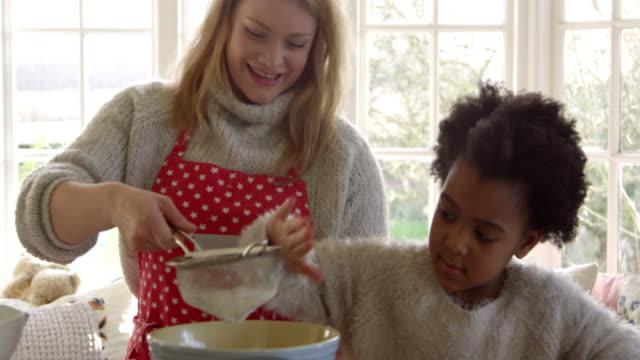 vídeos de stock e filmes b-roll de mother and daughter baking cake at home shot on r3d - avental
