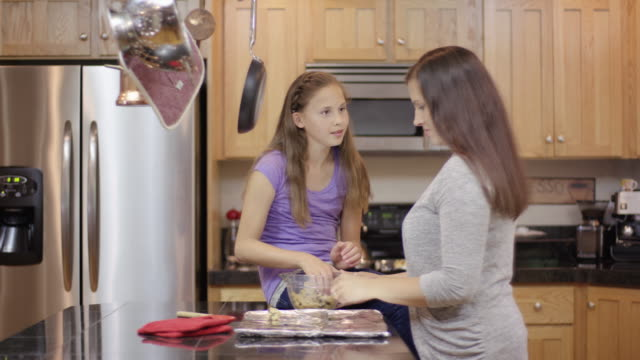 Mother and daughter baking together at home video
