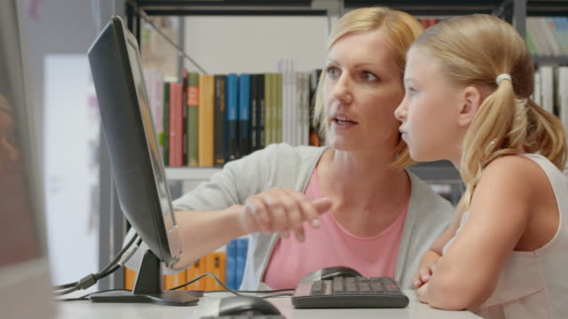DS Mother and daughter browsing on a computer in the library video