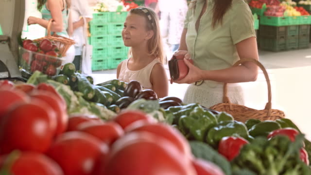Mother and daughter buying produce at marketplace video