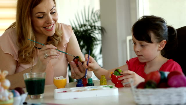 Mother and daughter coloring Easter eggs at home video