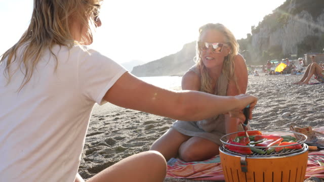 Mother and daughter cook vegetables over bbq, at beach They are surrounded by healthy foods while relaxing in sand, Liguria barbecue meal stock videos & royalty-free footage