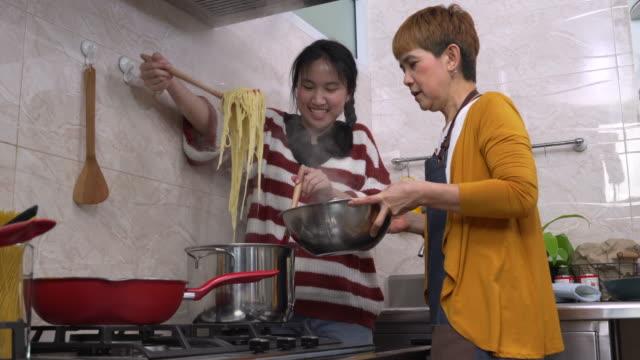 mutter und tochter kochen gemeinsam in der küche - gar gekocht stock-videos und b-roll-filmmaterial