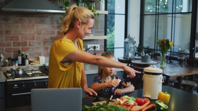 Mother and daughter cooking together Caucasian girl enjoying her time at home, standing with her mother in the kitchen, preparing vegetables, social distancing and self isolation in quarantine lockdown during coronavirus covid19 epidemic, in slow motion human relationship stock videos & royalty-free footage