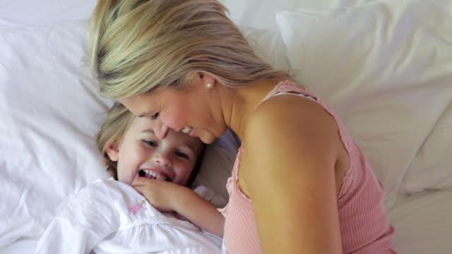 mother and daughter cuddling in bed - cosy pillows mother child bildbanksvideor och videomaterial från bakom kulisserna