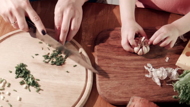 Mother and daughter cutting onion and garlic on wooden board video
