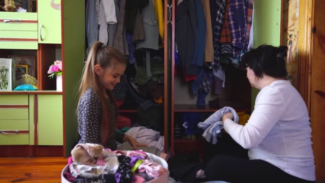 Mother and daughter decluttering wardrobe during quarantine Covid-19