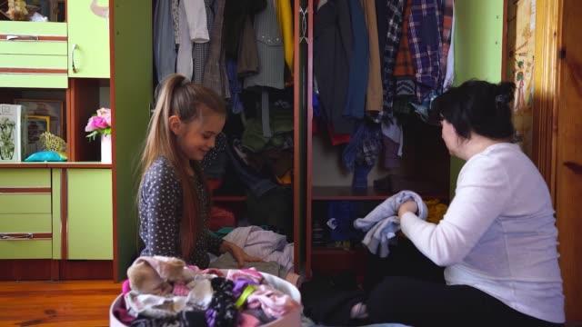 stockvideo's en b-roll-footage met moeder en dochter opruimen garderobe tijdens quarantaine covid-19 - opruimen