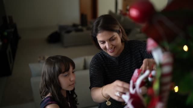 Mother and daughter decorating christmas tree and embracing at home