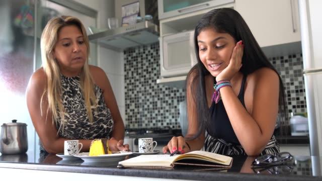 madre e figlia discutono di idee in cucina - to do list video stock e b–roll