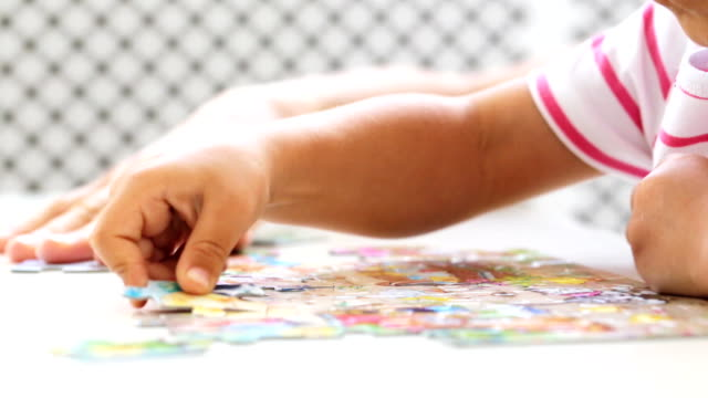 stockvideo's en b-roll-footage met moeder en dochter doen een puzzel samen in de lichte woonkamer - legpuzzel