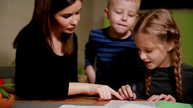 Mother and daughter doing a school homework assignment, a little boy watches it. Brother helps to do homework video