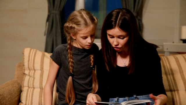 Mother and daughter doing a school homework assignment. Mom helps to deal with it video