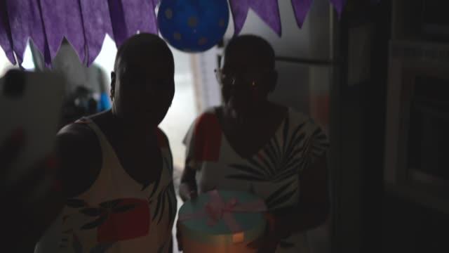 mor och dotter gör ett videosamtal på mobiltelefon på födelsedagsfest - birthday celebration looking at phone children bildbanksvideor och videomaterial från bakom kulisserna