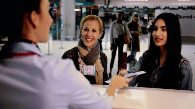 Mother and daughter doing check-in at airport before travel