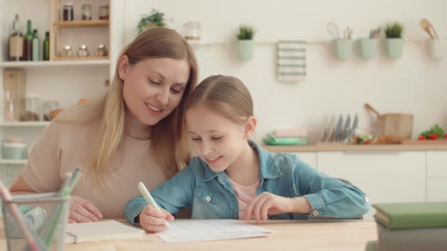 мать и дочь делают домашнее задание дома - covid testing стоковые видео и кадры b-roll