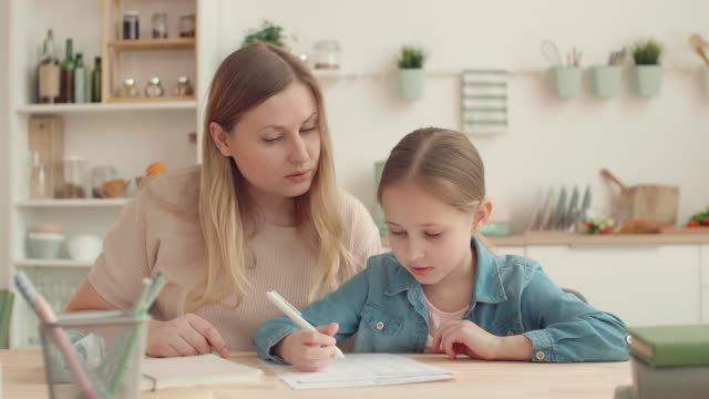 мать и дочь делают домашнее задание - covid testing стоковые видео и кадры b-roll