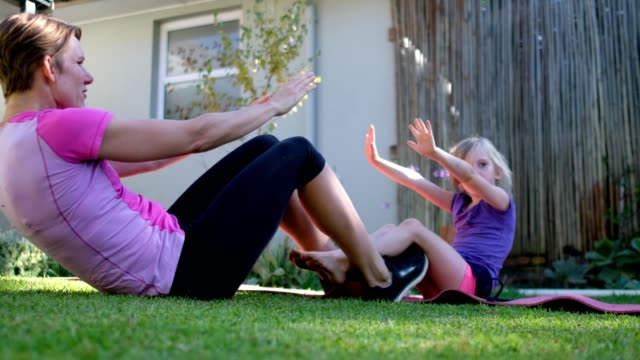 Mother and daughter doing some sit-ups outside in their yard A mother and daughter do some home gym workouts together. Being fit and active at home during the Corona Virus lockdown period healthy lifestyle stock videos & royalty-free footage
