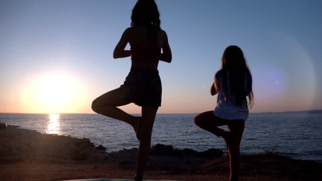 Mother and daughter doing yoga at sunset by the beach video