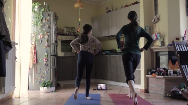 vídeos de stock e filmes b-roll de mother and daughter doing yoga exercises on rug at home - treino em casa