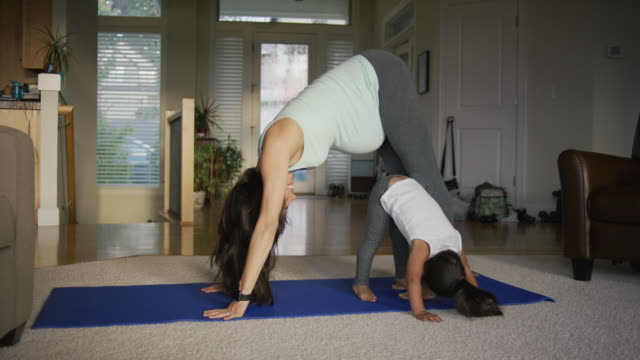 Mother and daughter doing yoga video