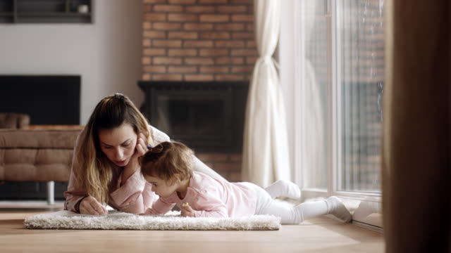 mother and daughter drawing on the floor at living room - matita colorata video stock e b–roll
