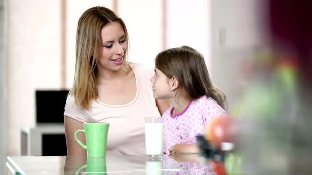 mother and daughter drinking milk and coffee - parent talking to child bildbanksvideor och videomaterial från bakom kulisserna