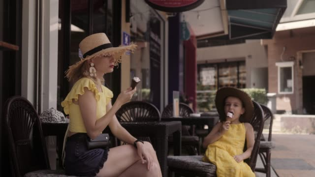 Mother and daughter eating icecream at the street cafe in summer day